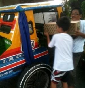 A volunteer unloads the box of relief goods.